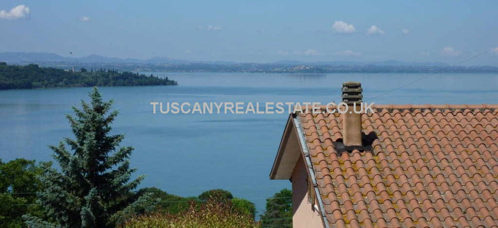 Lake Trasimeno real estate comprising a villa with stunning lake views located in the small Umbrian lakeside village of San Feliciano.