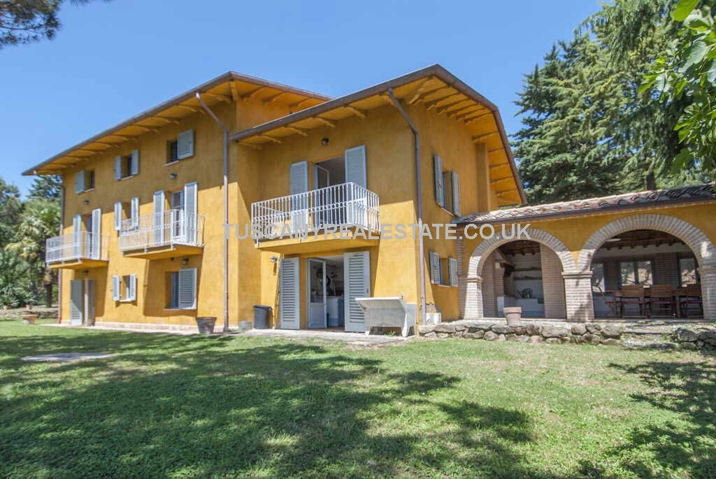 Charming Italian countryside villa for sale near to Città di Castello in Umbria and close to the Tuscan border. Restored, 5 bedrooms, swimming pool, 2.4 hectares (5.93 acres) land and gardens with 400 vines, 100 olive trees and 600 maritime pines