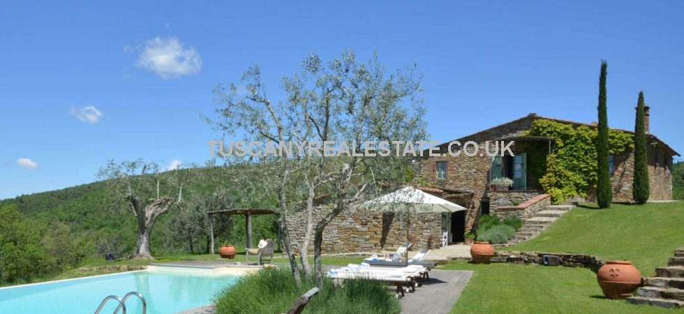 Near to Ambra in Tuscany, an impressive country house for sale, tastefully restored and occupying a private position amongst gardens with land, olive grove, swimming pool and panoramic views over the Tuscan hills.